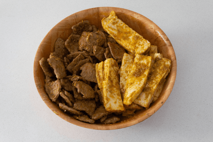 Soy protein and tofu marinating in a bowl.