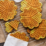 Pandan Waffles over a cooling rack with one in a paper bag.