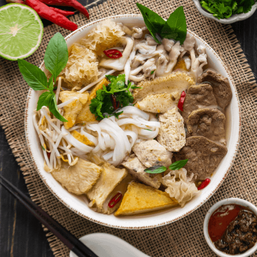 Pho Chay in a bowl surrounded by garnish and sauces in dishes.