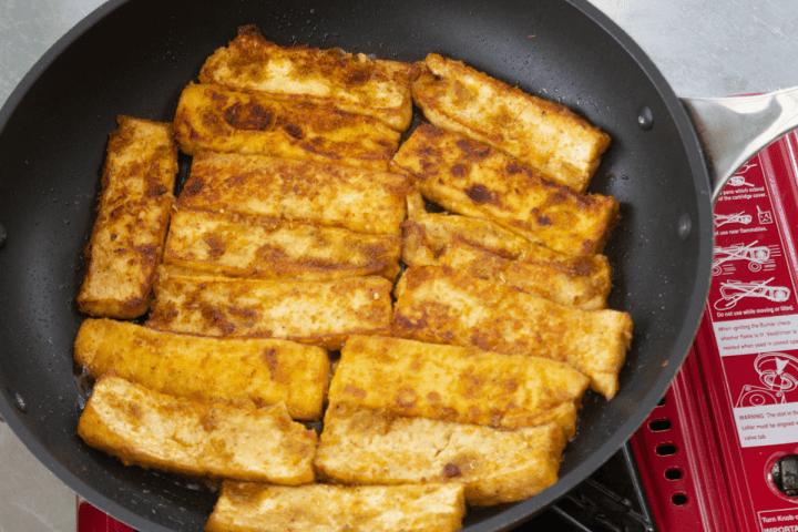 Marinated tofu searing in a pan.