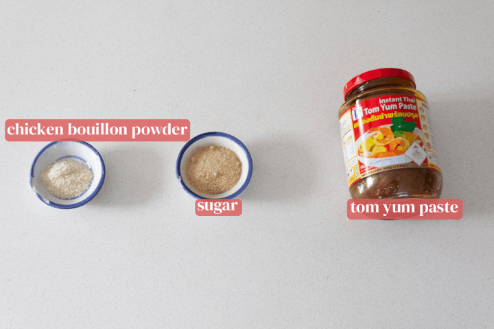 A jar of tom yum paste along with dishes of sugar and chicken bouillon powder.