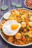 Tom Yum Fried Rice on a plate with a fried egg on it and a wedge of lemon.