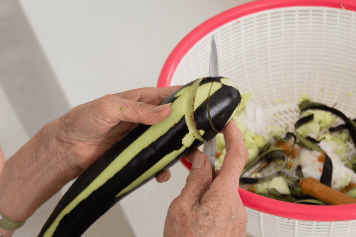 Hands holding onto an eggplant and slicing through it.