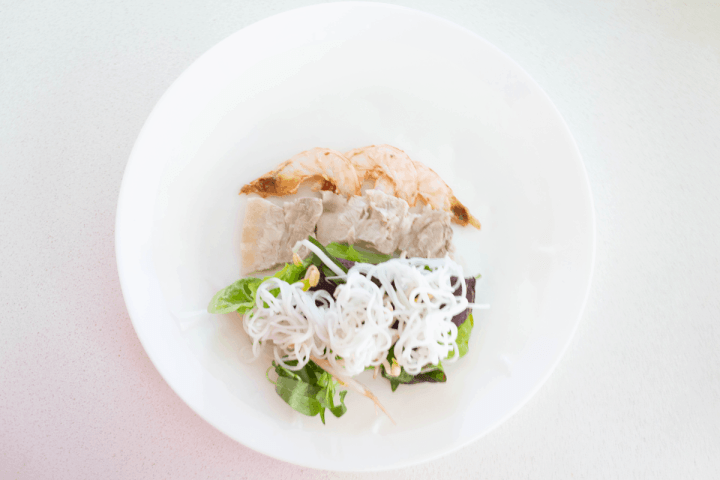 Prawns and pork belly slices above noodles and herbs on rice paper on a plate.