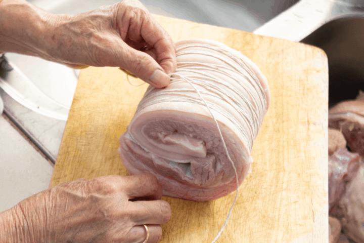 A hand using twine to tie around a rolled pork belly slab.