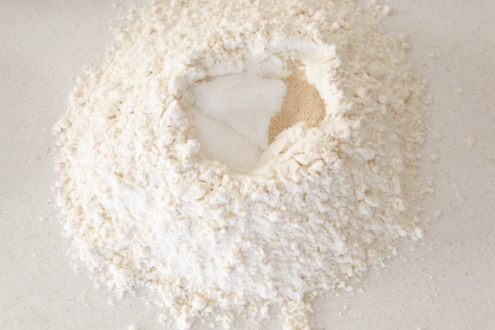 Yeast, sugar and salt in a well of flour.