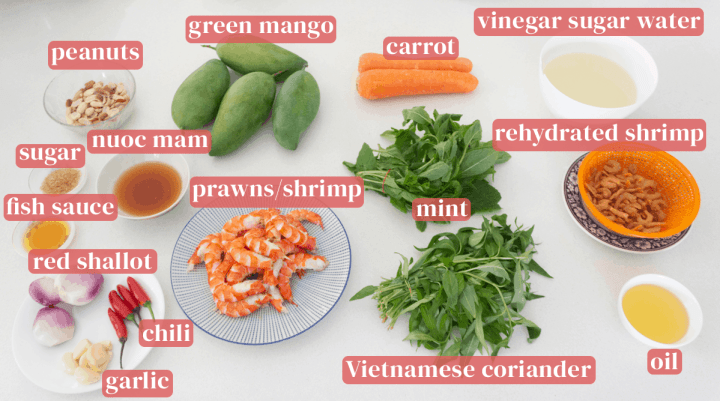 Green mangoes, carrots, vinegar sugar water in a bowl, rehydrated shrimp in a colander, Vietnamese coriander, mint, prawns on a plate, nuoc mam, sugar and fish sauce in dishes, red shallots, garlic and chili.