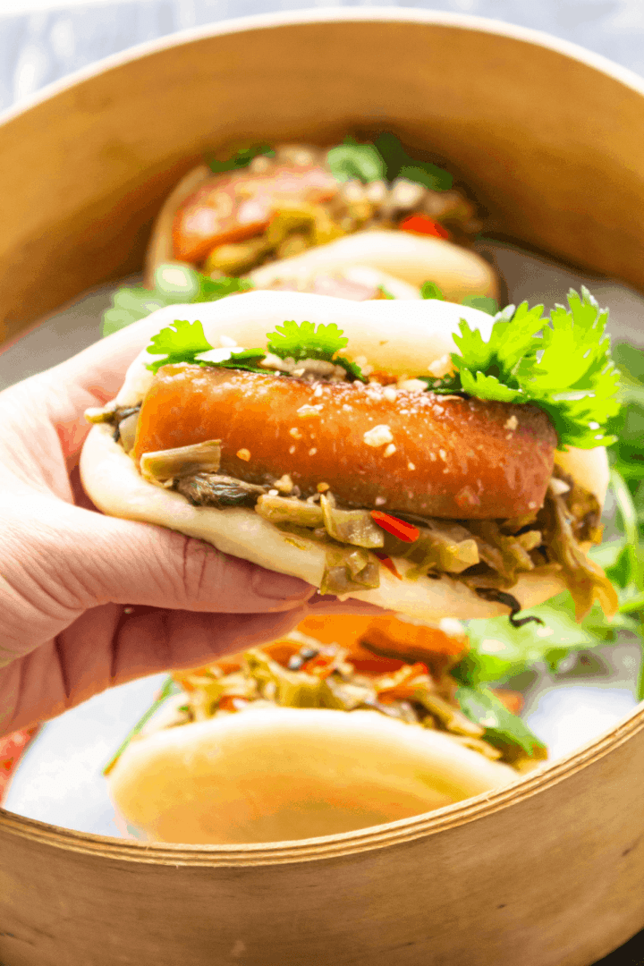 Gua Bao Buns in a steamer with one being held by a hand.