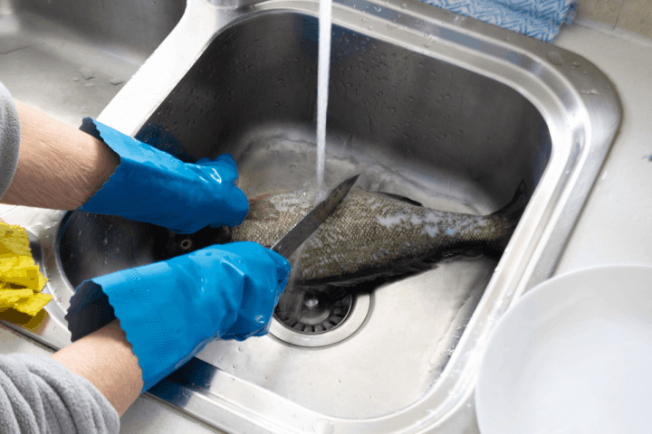 A cleaver scaling fish in a sink under running tap water.