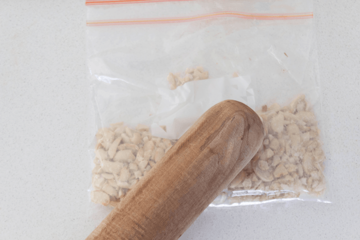 Smashed peanuts in a ziplock bag with a wooden rolling pin pressed on it.