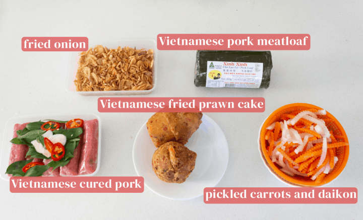 Fried onion in a box along with Vietnamese pork meatloaf, a colander of pickled vegetables, a plate of Vietnamese fried prawn cake and a container of Vietnamese cured pork.
