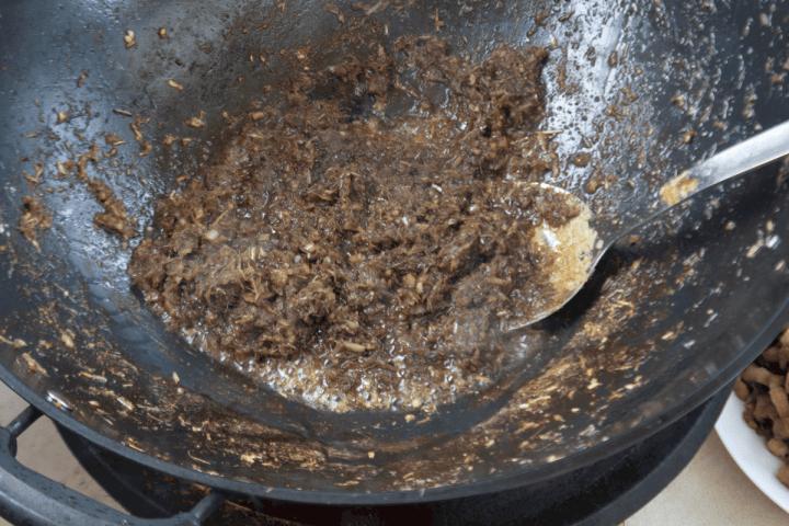 Lemongrass and shrimp paste in a wok.