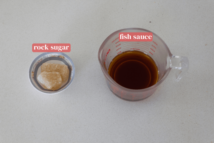 Rock sugar in a dish along with fish sauce in a jug.