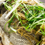 Steamed with with ginger and shallots on a plate.