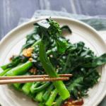 Chopsticks holding up a Chinese broccoli.
