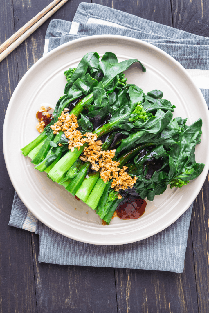 Chinese broccoli with oyster sauce on a plate topped with browned garlic.