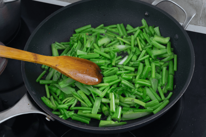 Chinese broccoli stem segments in a wok with a wooden spoon.