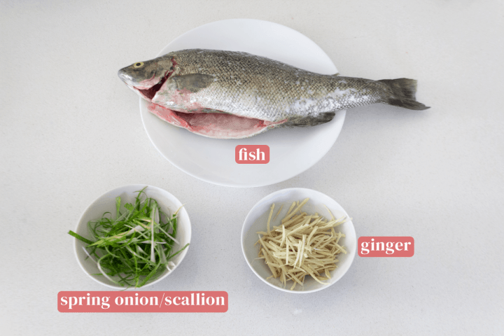 A fish on a plate along with finely chopped spring onion and ginger in bowls.