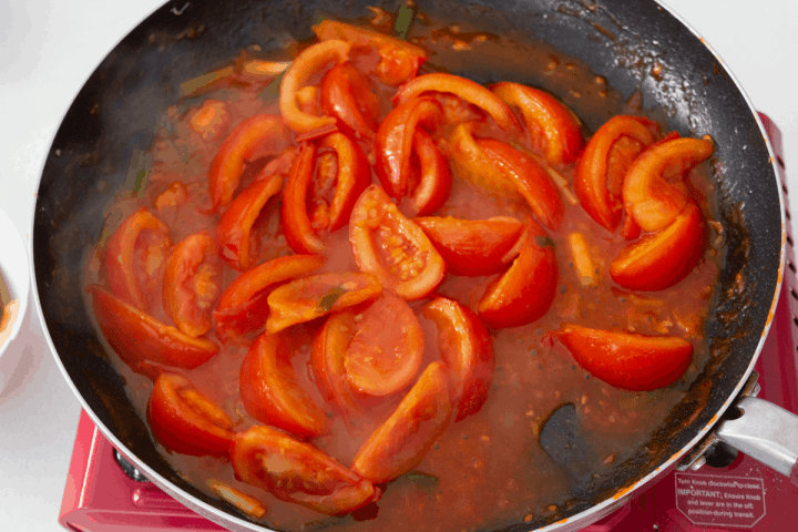 Quartered tomatoes cooking in a pan.