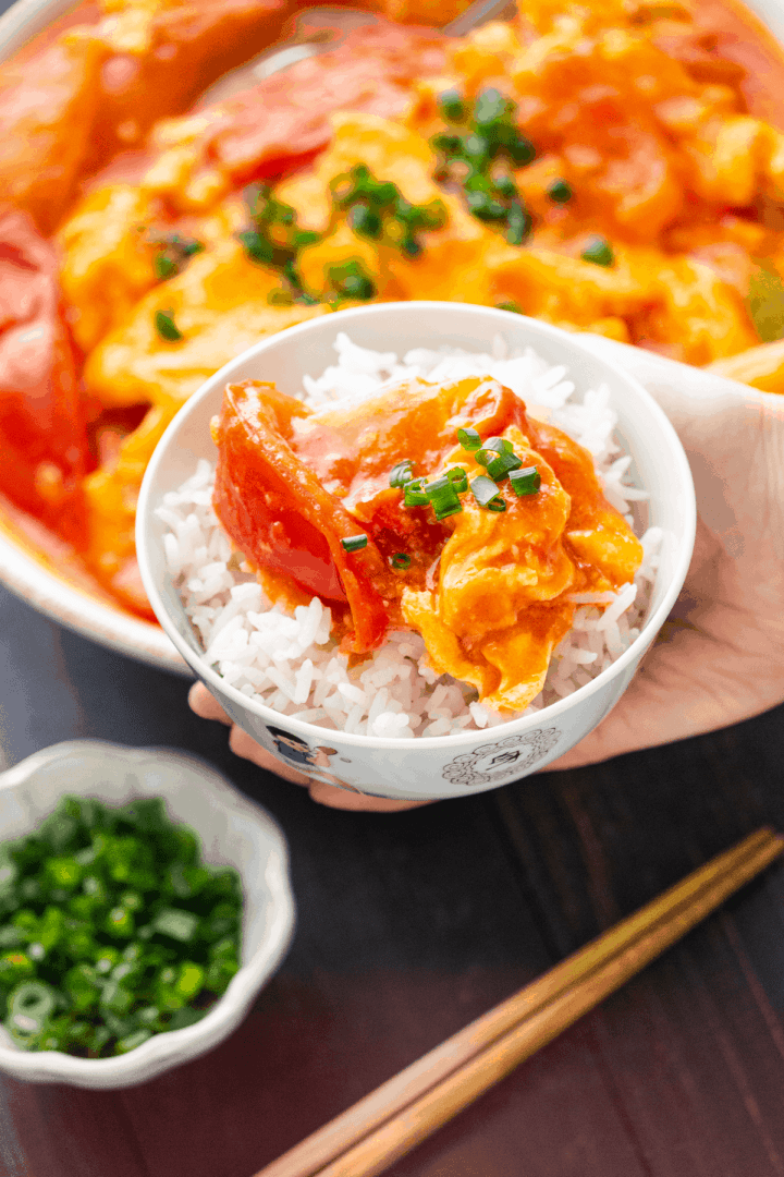 Egg and Tomato Stir Fry in a bowl of rice held by a hand.