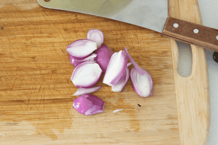 Sliced red shallots on a chopping board next to a cleaver.