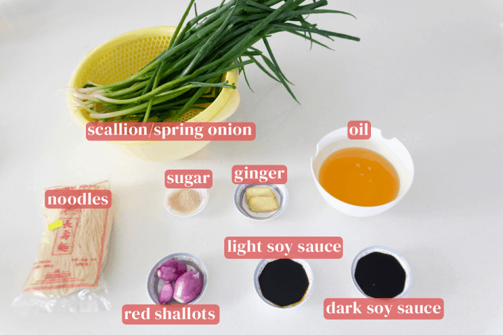 Scallions in a colander along with a bag of noodles, dishes of ginger, sugar, red shallots, light soy sauce and dark soy sauce and a bowl of oil.