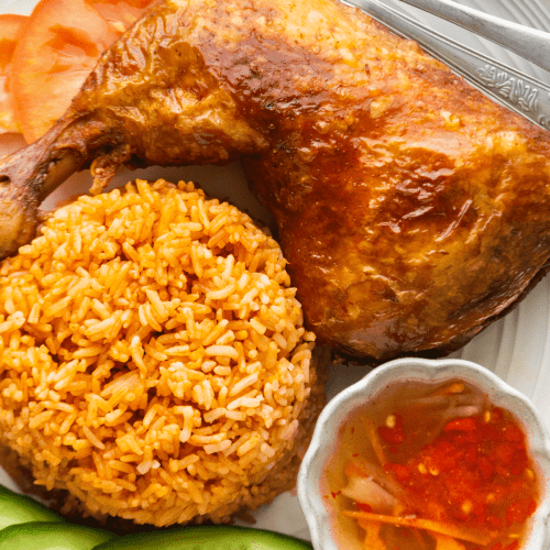Vietnamese Crispy Skin Chicken on a plate with sliced cucumbers along with tomato rice and a dish of Vietnamese dipping sauce.