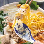 Chopsticks lifting up some noodles in a bowl with a spoon.