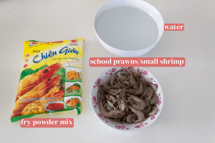 A bowl of water and a bowl of school prawns along with a bag of fry powder mix.