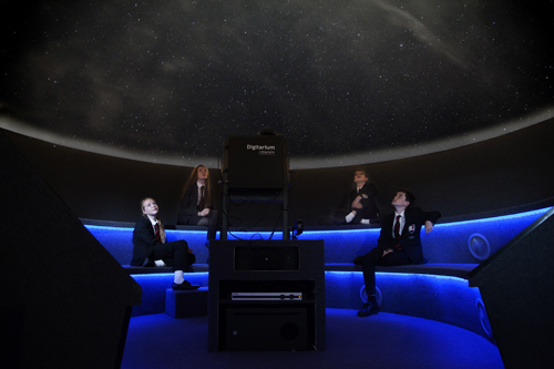 The interior of a planetarium, 4 students sitting looking up, stars on the domed ceiling, projector in centre.