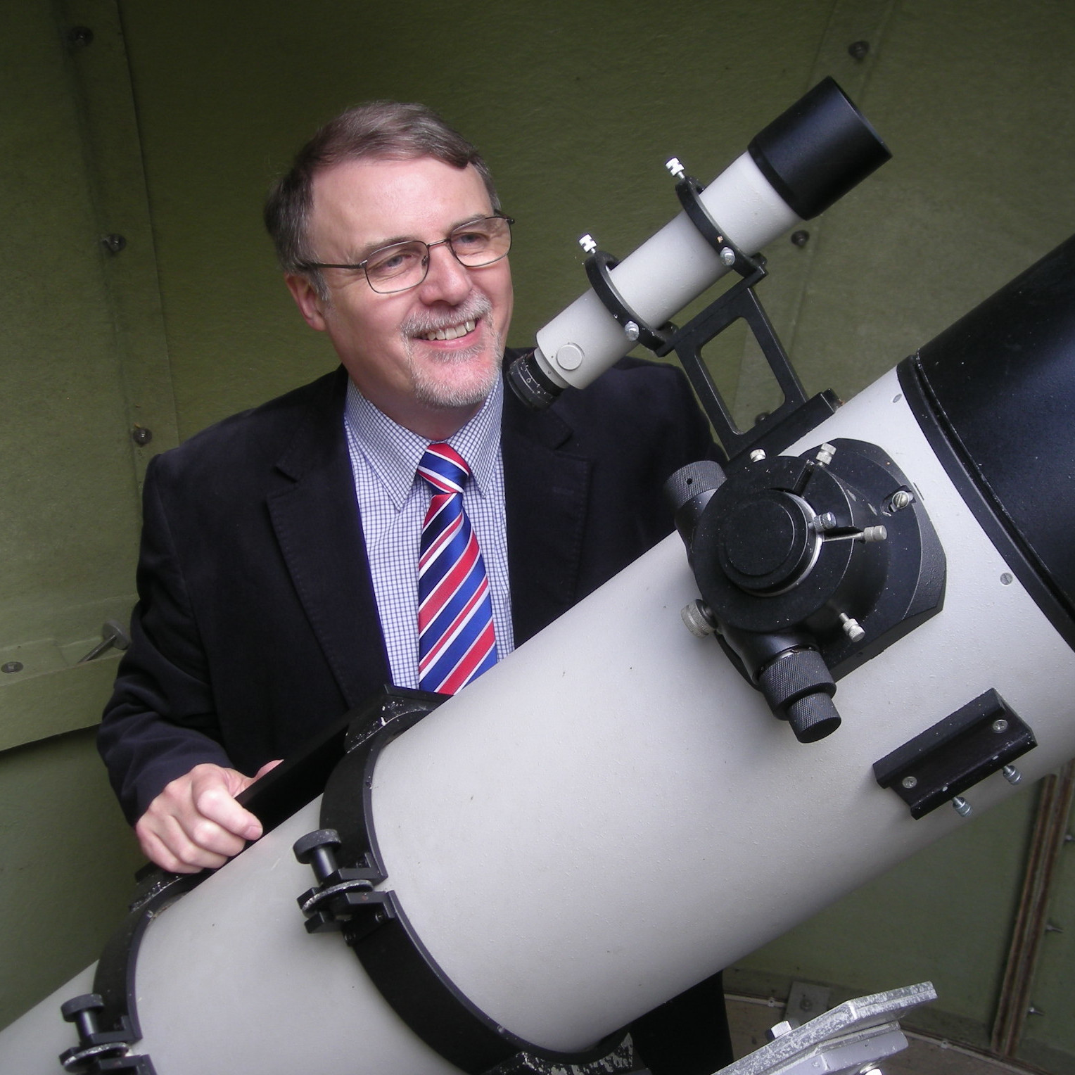 Laurence Anslow behind a large telescope.