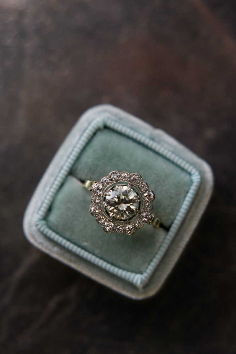 A round diamond engagement ring with diamond cluster sits in a vintage box