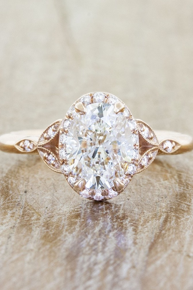 An oval diamond engagement ring with leaf shoulders and gold band sits on a wooden table