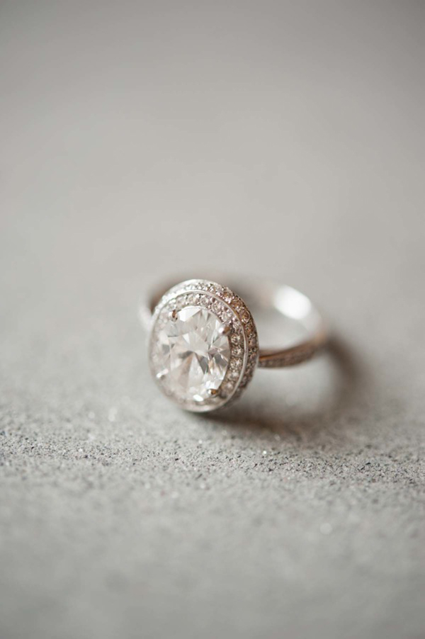 A vintage style oval diamond ring with halo diamonds sits on a table