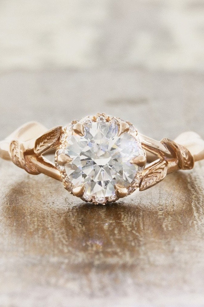 A solitaire diamond engagement ring with a gold foliage band sits on a wooden table