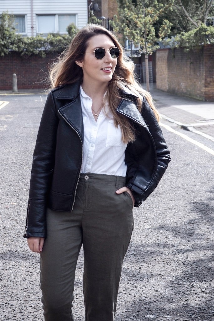 Woman walking down a London street wearing linen trousers, a white top and wearing a black leather jacket   Wolf & Stag