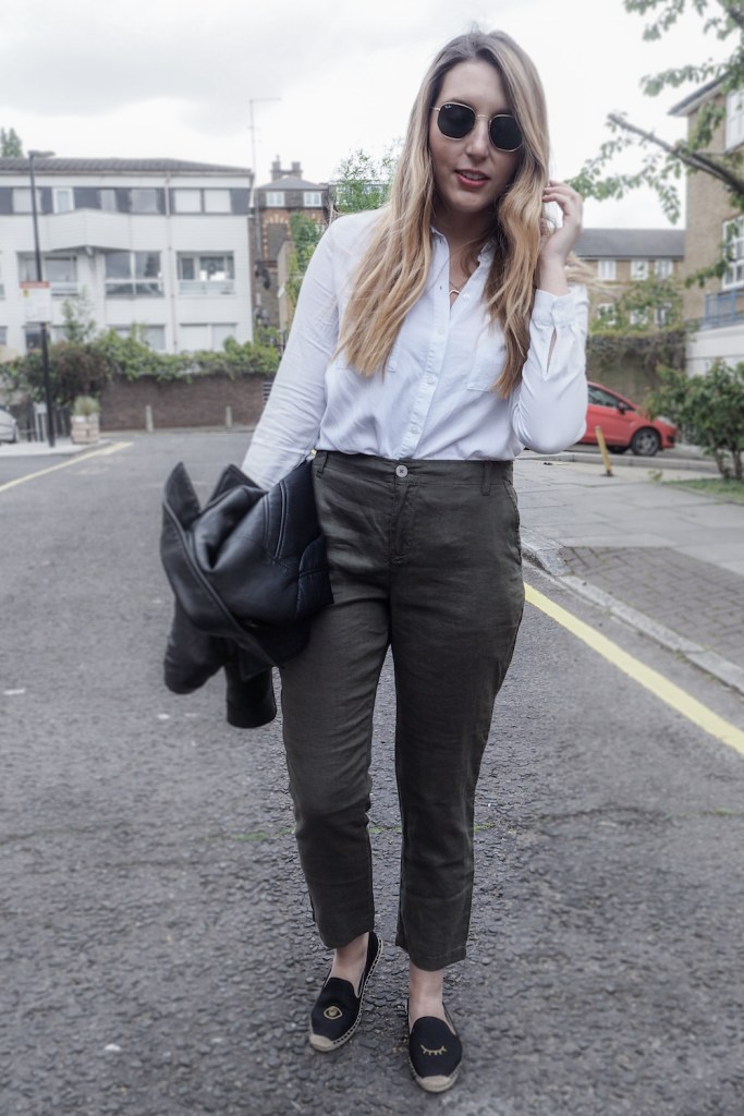 Woman walking down a London street wearing linen trousers, a white top and holding a leather jacket   Wolf & Stag