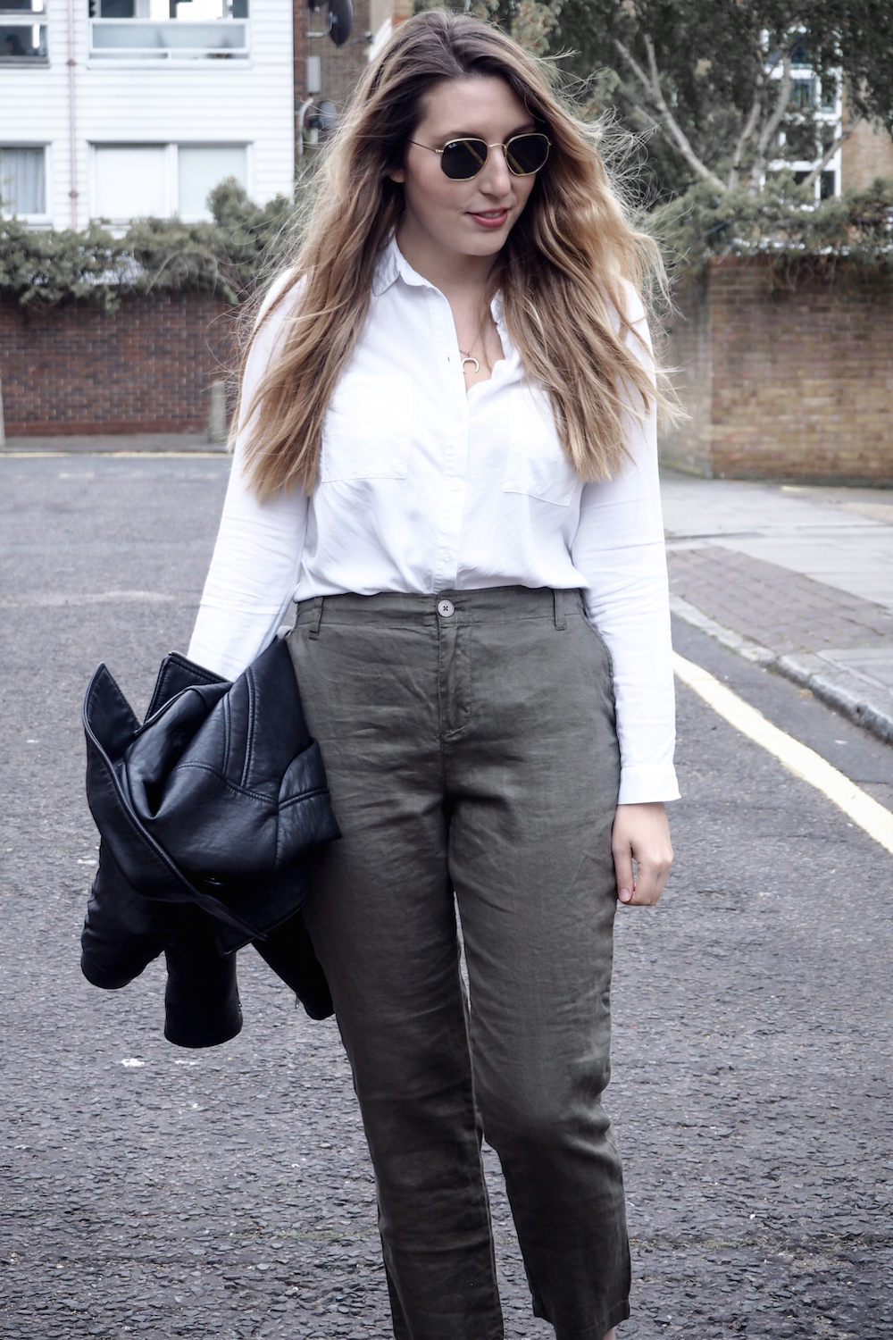 A woman walking down a London street wearing linen trousers, a white top and holding a leather jacket | Wolf & Stag