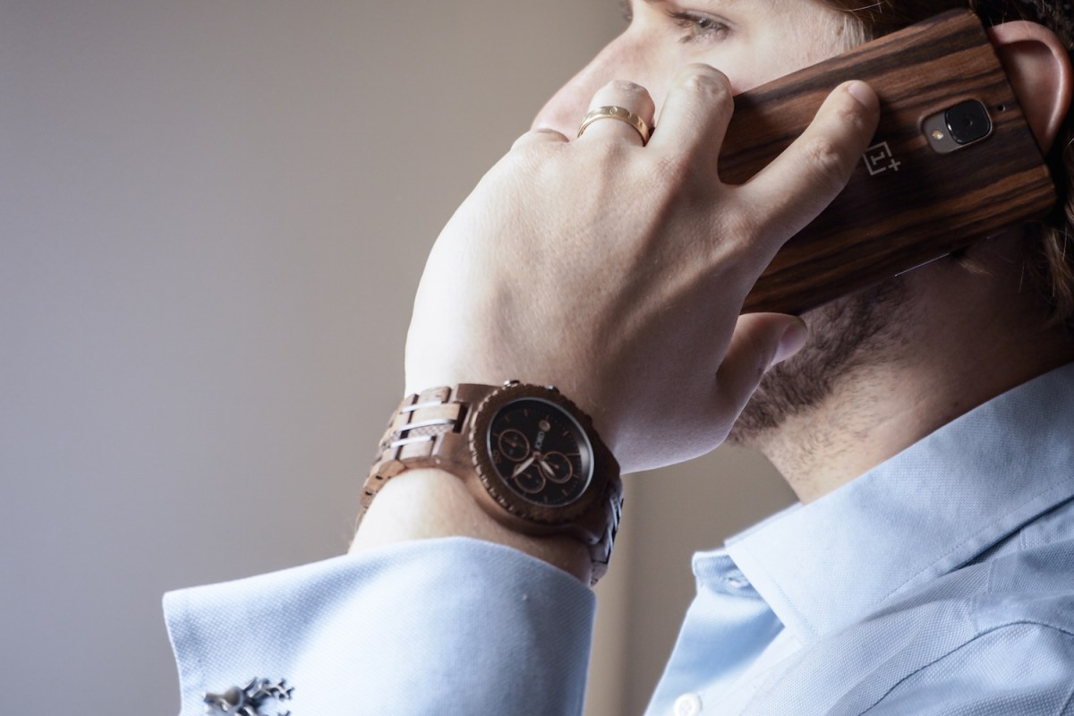 Man in blue shirt wearing wooden JORD Conway watch makes phone call
