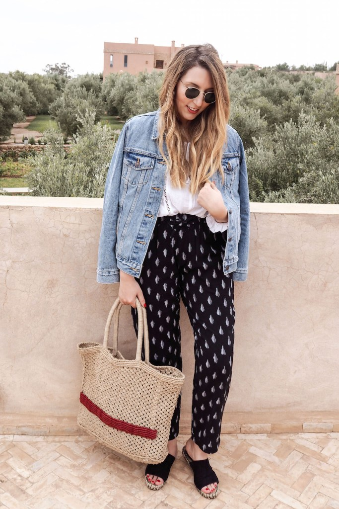 Summer travel outfit of Kirei ikat trousers, Urban Outfitters white blouse, Levis denim jacket, Mango jute tote bag, Ray-Ban sunglasses | Wolf & Stag