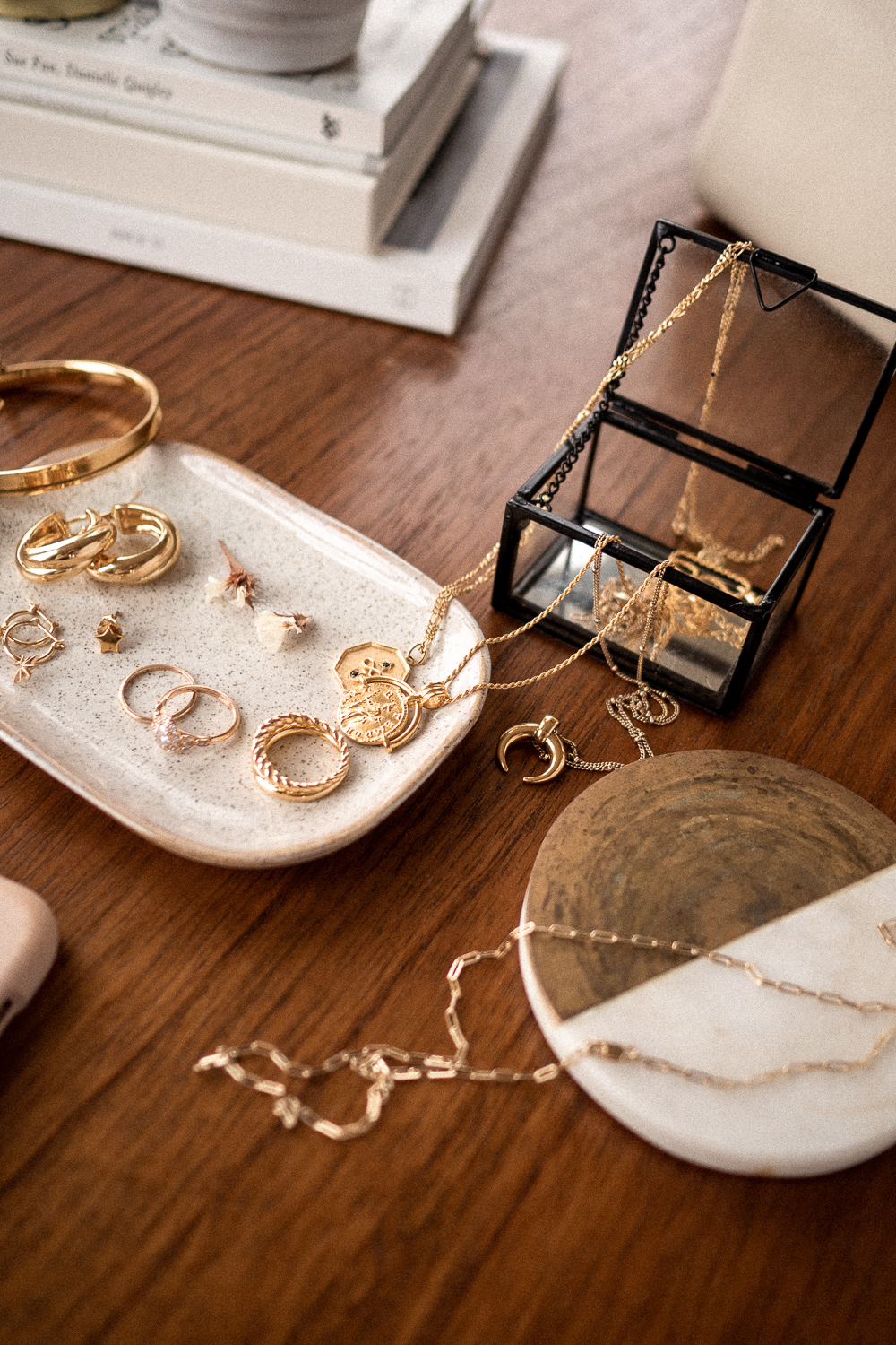 Gold necklaces, gold rings, gold earrings, and gold bracelets all laid out on display in my capsule jewelry collection