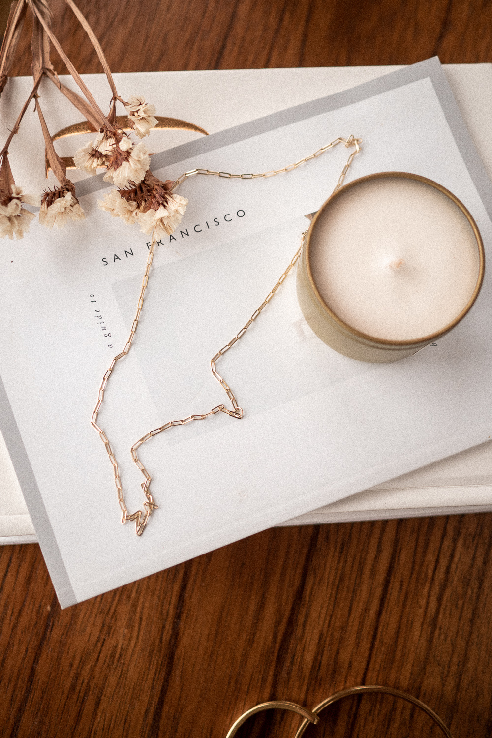 A closeup of the medium chain gold necklace from AU-Rate on a book, a part of my capsule jewelry collection