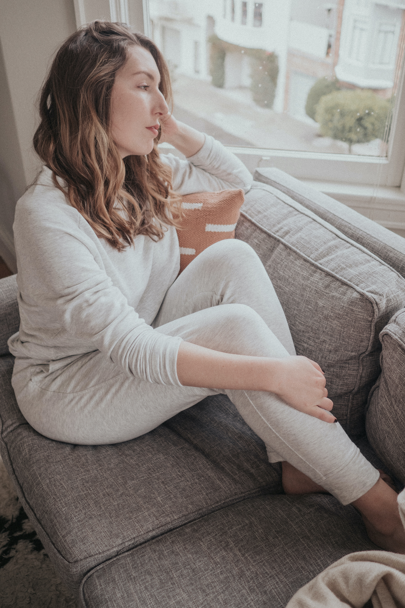 Erin Pollard sits on an unmade bed, looking out the window, wearing Lou & Grey Signaturesoft Plus Upstate Sweatpants and Sweatshirt in Light Heather Grey