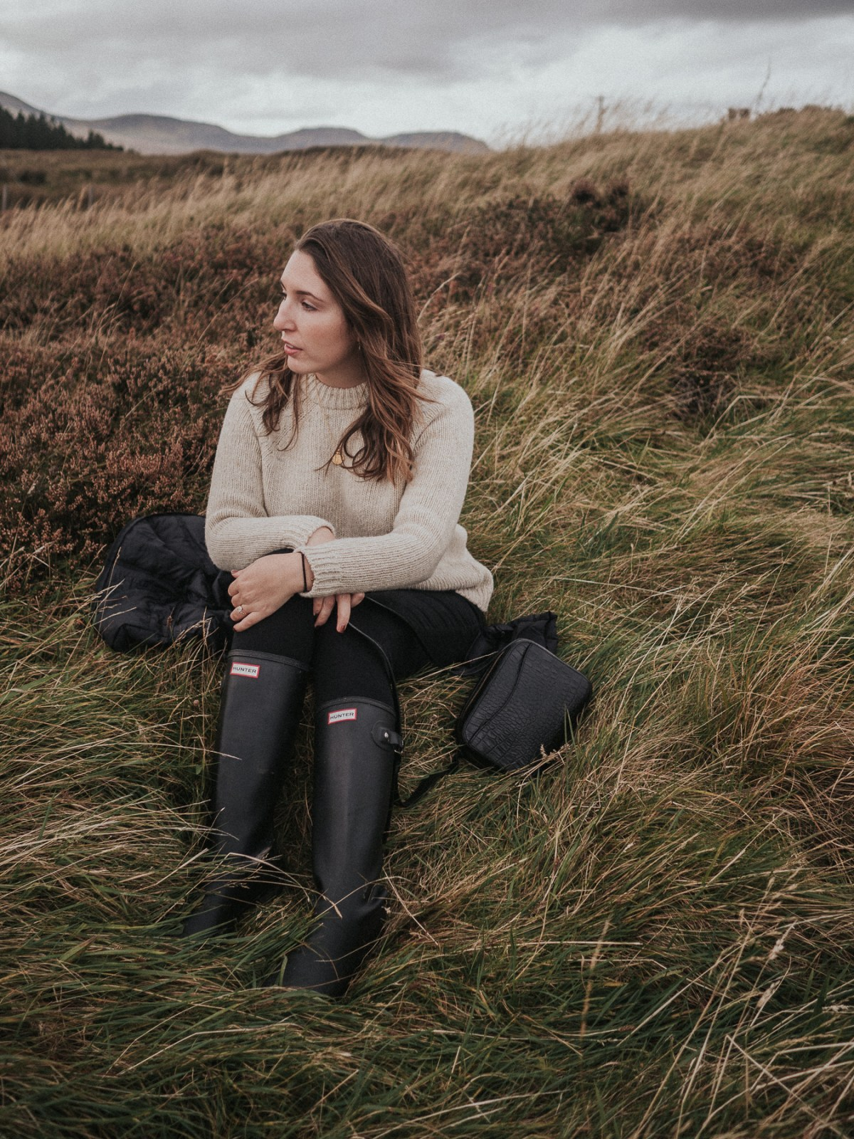 Sitting in a Scottish field wearing a Finisterre sweater, Hunter boots, and a Cuyana croc bag | A One Week Scottish Highlands Travel Itinerary | a detailed account of exactly what we did to make the best 7 day roadtrip through the Scottish Highlands | W&S