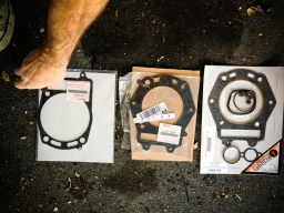 Left to right: the OEM metal base gasket, notice the golden rivet at the upper right, the OEM metal head gasket, a cheaper aftermarket head gasket