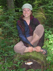 instructor-Megan-Damofle-perched-on-log-in-forest.jpg