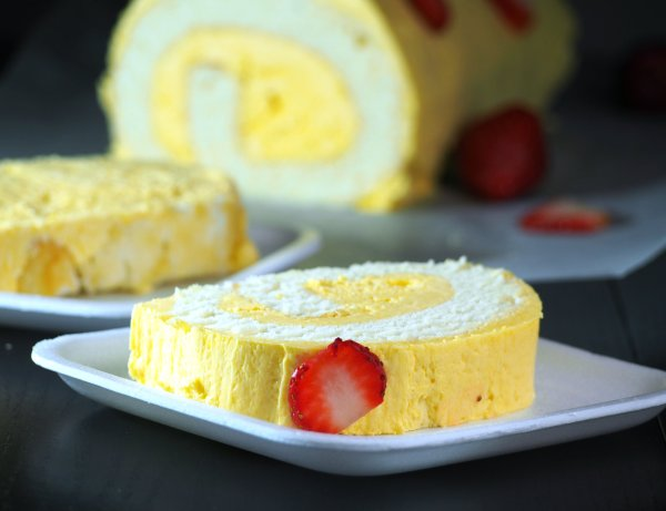 Mango cake roll that is soft and fluffy and iced with mango Swiss meringue buttercream.