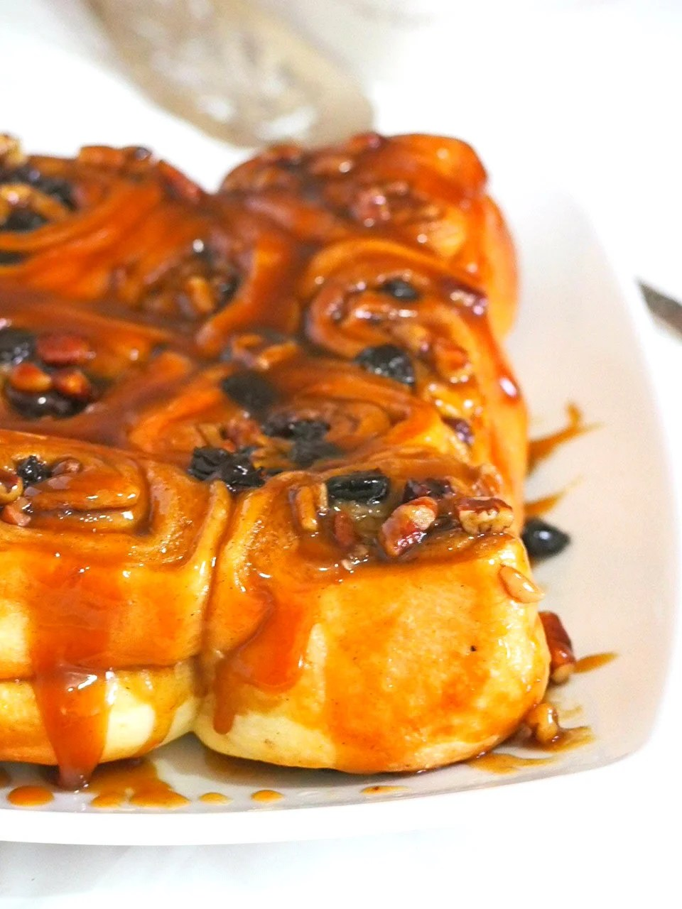 These sticky buns are loaded with pecan nuts and raisins, and covered in a sweet and sticky brown sugar topping. These are the ultimate cinnamon rolls using brioche dough that is packed with  flavorful cinnamon sugar filling.