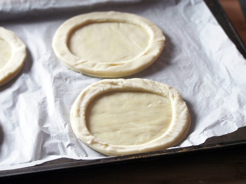 Set aside the centers but take the outer rings, and center them on top of the other 4 whole circles on the baking sheet.