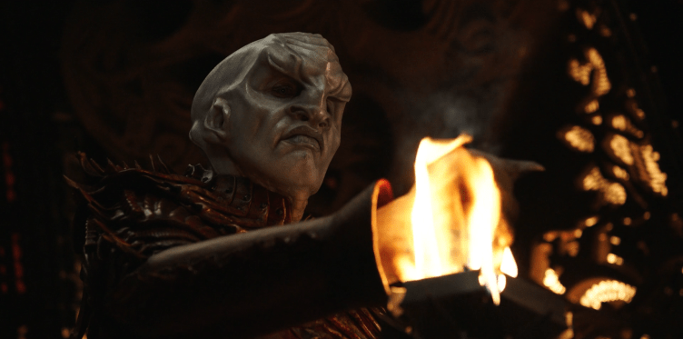 Voq, a Klingon, puts his hand in a ceremonial flame.